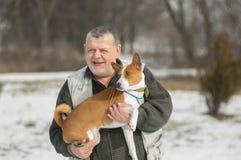 Ritratto all'aperto dell'uomo senior caucasico che prende il suo cane adorabile di basenji Fotografia Stock