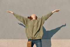 Ritratto all'aperto della ragazza teenager felice con le mani su ed occhi chiusi, fondo soleggiato grigio della parete, emozione  fotografie stock libere da diritti