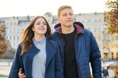 Ritratto all'aperto delle coppie felici di abbraccio, dell'uomo bello e della donna camminanti, citt? di sera del fondo immagini stock