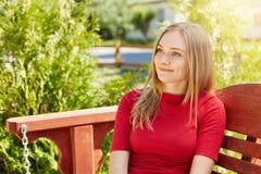 Ritratto all'aperto di abbastanza femminile con capelli giusti diritti e l'aspetto piacevole che portano maglione rosso che si si Fotografie Stock Libere da Diritti