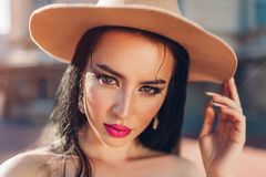 Ritratto all'aperto di bella donna castana con il cappello d'uso di trucco Modello femminile sexy fotografia stock libera da diritti