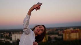 Ritratto all'aperto di bella ragazza che prende un selfie sul tetto fotografia stock libera da diritti