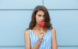 Ritratto all'aperto di giovane bella donna castana felice in vestito a strisce da estate che posa con la lecca-lecca rossa del cu Fotografia Stock Libera da Diritti