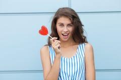Ritratto all'aperto di giovane bella donna castana felice in vestito a strisce da estate che posa con la lecca-lecca rossa del cu Fotografia Stock