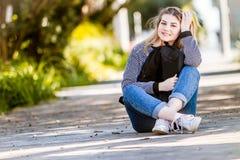 Ritratto all'aperto di giovane ragazza teenager sorridente felice sul BAC naturale immagine stock