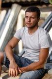 Ritratto all'aperto di un giovane bello in jeans e maglietta grigia Immagine Stock
