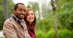 Ritratto all'aperto giovani delle coppie interrazziali romantiche e felici in parco Fotografia Stock Libera da Diritti