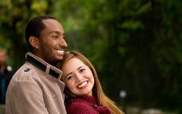 Ritratto all'aperto giovani delle coppie interrazziali romantiche e felici in parco Fotografia Stock