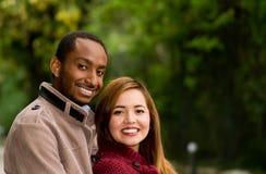 Ritratto all'aperto giovani delle coppie interrazziali romantiche e felici in parco Immagini Stock Libere da Diritti