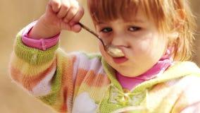 Ritratto all'aperto: La bambina sveglia mangia con il cucchiaio stock footage