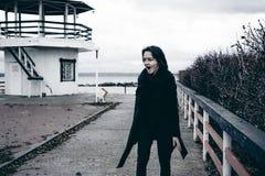 Ritratto alla moda di giovane donna castana in vestiti neri, jeans maglietta, cappotto ed occhiali da sole, in un umore triste di fotografia stock libera da diritti