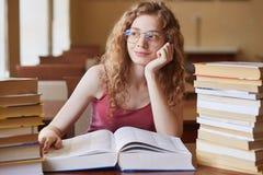 Ritratto alto vicino dei capelli ricci sexy dello studente del wirh attraente premuroso della ragazza, in vetri che si siedono fr fotografia stock