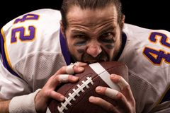 Ritratto alto vicino del giocatore aggressivo aggressivo del giocatore di football americano che morde la sua palla immagini stock