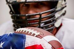 Ritratto alto vicino del giocatore di football americano in casco con la palla e della bandiera americana fiera del suo paese, su fotografia stock
