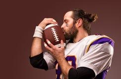 Ritratto alto vicino del giocatore di football americano che bacia delicatamente la palla fotografia stock libera da diritti
