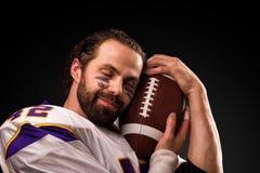 Ritratto alto vicino del giocatore di football americano che tiene delicatamente la palla fotografia stock