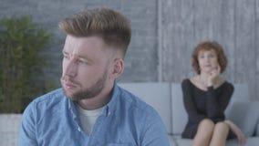 Ritratto alto vicino del giovane infelice triste che distoglie lo sguardo nella priorit? alta La figura vaga di signora matura ch archivi video