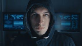 Ritratto alto vicino del programmatore anonimo del pirata informatico in maglia con cappuccio nera a fondo del centro cyber di si stock footage