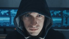 Ritratto alto vicino del programmatore del pirata informatico di professionista IT in maglia con cappuccio nera al centro cyber d archivi video