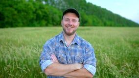 Ritratto alto vicino dell'agricoltore dell'uomo con la barba che guarda alla macchina fotografica nel giacimento di grano Fronte  archivi video