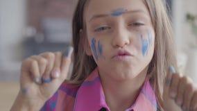 Ritratto alto vicino della bambina reale di divertimento Bambina emozionale sveglia con dipinto nel fronte della pittura di color stock footage