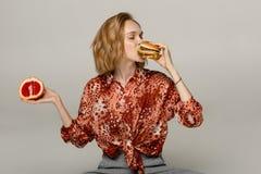 Ritratto alto vicino della ragazza bionda graziosa che che mangia hamburger immagini stock