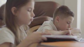 Ritratto alto vicino della sorella e dei suoi taccuini sfogliare gemellati del fratello stanco con compito esaurito dopo scuola stock footage