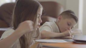 Ritratto alto vicino della sorella gemellata e dei suoi taccuini sfogliare gemellati del fratello stanco con compito esaurito dop stock footage