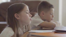 Ritratto alto vicino della sorella gemellata e dei suoi taccuini sfogliare gemellati del fratello stanco con compito esaurito dop archivi video
