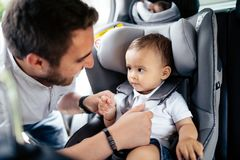 Ritratto alto vicino di giovane padre che fissa bambino nel sedile del bambino dell'automobile immagine stock