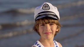 Ritratto alto vicino di poco ragazzo sorridente che esamina macchina fotografica sull'oceano del mare della spiaggia Estate di es stock footage