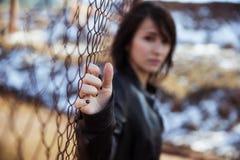 Ritratto anonimo della donna sopra la rete fissa Fotografia Stock