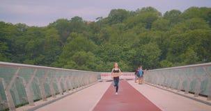 Ritratto anteriore del primo piano di giovane pareggiatore femminile sportivo grazioso che corre sul ponte in città urbana all'ap stock footage