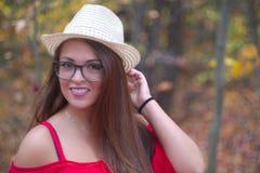 Ritratto arancio della foresta del vestito rosso da autunno di vetro del cappello della giovane donna fotografie stock libere da diritti