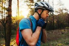 Ritratto attraente del ciclista maschio barbuto bello che indossa casco protettivo prima della corsa, stante sulla foresta contro immagine stock libera da diritti