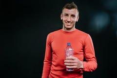 Ritratto attraente del colpo dell'uomo caucasico muscolare sorridente bello che porta abiti sportivi rossi con la bottiglia di ac Immagine Stock Libera da Diritti
