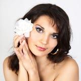 Ritratto attraente della donna con il fiore bianco Immagine Stock