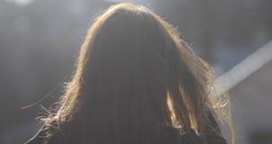 Ritratto attraente di giovane donna castana con il bello sorriso, con i capelli lunghi ventosi, sul fondo del parco osservare archivi video