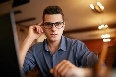 Ritratto autentico di giovane uomo d'affari sicuro che esamina macchina fotografica con il computer portatile in ufficio Uomo dei fotografia stock