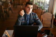Ritratto autentico di giovane uomo d'affari sicuro che esamina macchina fotografica con la compressa e lo smartphone del computer immagine stock