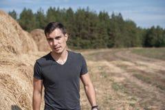 Ritratto autentico frontale di un giovane in una maglietta grigia sui precedenti di un campo con i mucchi di fieno fotografia stock