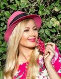 Ritratto Bella ragazza bionda in un cappello Tenuta del fiore in sua mano su aria aperta Dietro il suo fogliame verde È illuminat fotografie stock
