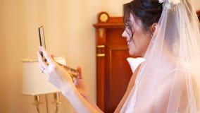Ritratto bella sposa in velo bianco che tiene uno specchio in sue mani, esaminante la nello specchio, sorridente E archivi video