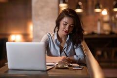 Ritratto bello e donna di affari bella che scrive le note e che lavora al suo computer portatile nel ristorante moderno Fotografie Stock Libere da Diritti