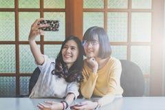 Ritratto bello sorridere teenager asiatico della donna, felice, divertimento e selfie con il suo smartphone Fotografie Stock Libere da Diritti