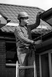 Ritratto in bianco e nero del lavoratore che ripara il tetto della casa Fotografie Stock Libere da Diritti