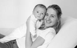 Ritratto in bianco e nero della giovane donna sorridente che si trova sul letto e che tiene i suoi 3 mesi del neonato Fotografia Stock