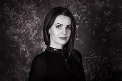 Ritratto in bianco e nero di bella giovane donna castana che si siede nella camera da letto Fotografia Stock