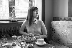 Ritratto in bianco e nero di una ragazza in un caffè che guarda dalla finestra Fotografia Stock