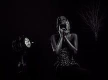 Ritratto in bianco e nero surreale del modello afroamericano sexy con la parrucca lucida dell'oro e del trucco che posa alla macc Fotografie Stock Libere da Diritti